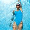 Hrbtno 1: Plavalec leži iztegnjen v hrbtnem položaju na vodni gladini, z glavo med vzročenimi rokami.