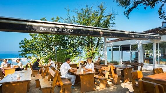 Pizzeria Bukaleta se nahaja v majhnem zalivu ob morju.