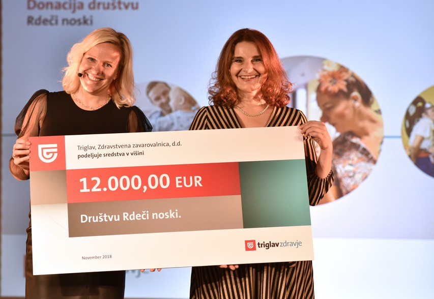 Eva Škofic Maurer, klovnesa in ustanoviteljica društva Rdeči noski, je prejela donatorski ček za 12.000 evrov. Podelila ga je mag. Meta Berk Skok, predsednica uprave Triglav, Zdravstvena zavarovalnica, d.d.